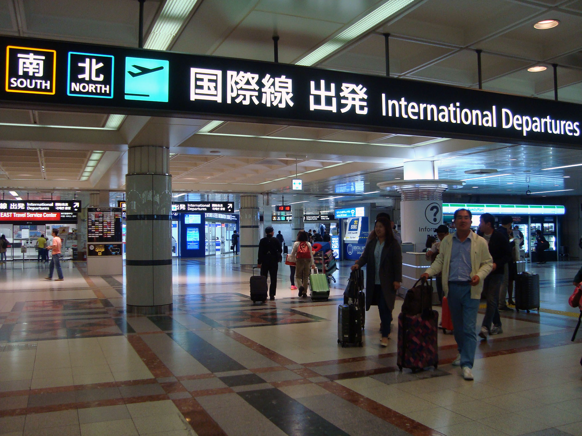 "North wing and south wing are indicated by pictograms instead of letters to save the space and display the large letter ""International Departures""."